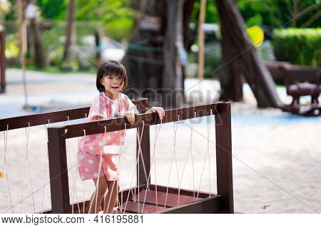 Girl Climbs Wooden Bridge. Child Play On Rope Bridge In Playground. Practice Balance. Happy Kid Laug