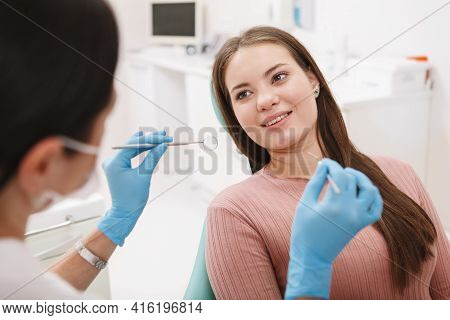 Young Beautiful Woman Smiling At Her Dentist, Getting Dental Exam