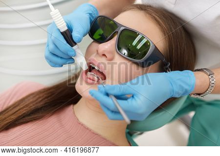 Close Up Of A Woman Wearing Protective Eyeglasses, Getting Dental Cleaning By Professional Hygienist