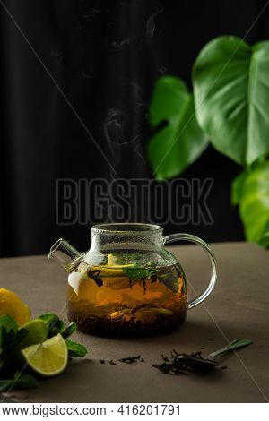 The Process Of Brewing Black Tea With Herbs, Glass Teapot With Black Tea, Lemon, Lime And Mint Drenc