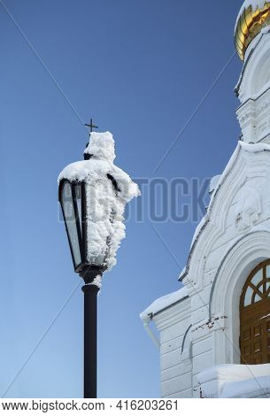 Close-up Of A Street Lamp With A Thick Layer Of Frost On The Glass. The Lantern Is Located Next To T