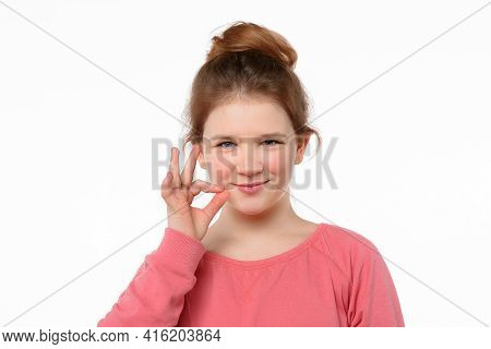 Your Secrets Safe With Me Concept. Young Girl Showing Zip Gesture As If Shutting Mouth On Key. Studi