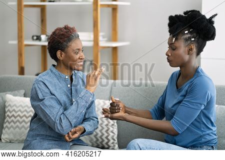 Deaf African American Using Sign Language At Sofa