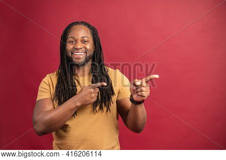 Black Man With Beard Dreadlocks Looking At Camera Smiling With The Index Of Both Hands Pointing To T