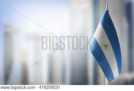 A Small Flag Of Nicaragua On The Background Of A Blurred Background