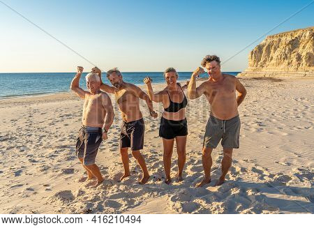 Group Of Mature Happy Active Adults Having Fun In The Beach. Long Time Friends