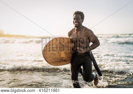 Male Afro Surfer Having Fun Surfing During Sunset Time - African Man Enjoying Surf Day - Extreme Spo
