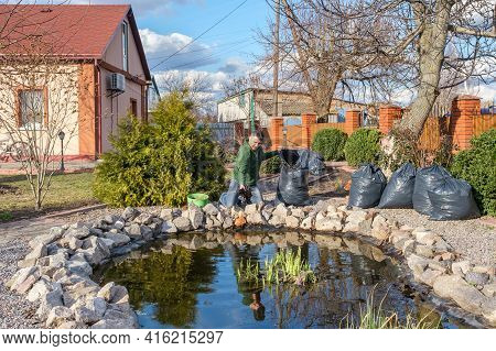 Mature Adult Caucasian Man Cleans A Garden Pond From Water Plants And Falling Leaves And Puts It In