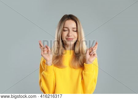 Woman With Crossed Fingers On Light Grey Background. Superstition Concept
