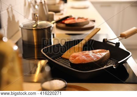 Frying Pan With Fresh Salmon Steak On Cooktop