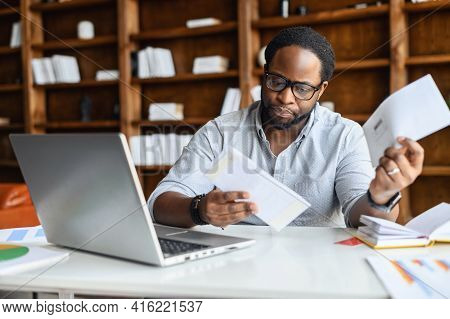 Worried African-american Looking Through Correspondence, A Guy Holds Envelopes In Hands, Got Fine By