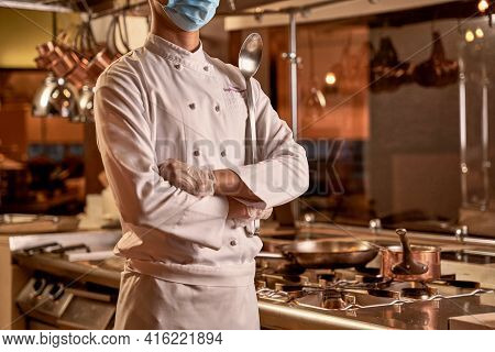 Proud Chef Standing With Crossed Arms In Kitchen