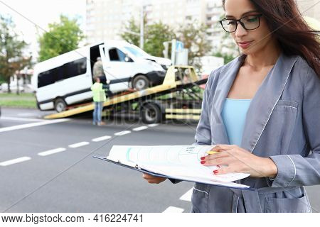 Insurance Agent Standing Near Wrecked Car On Tow Truck