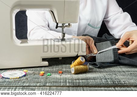 Seamstress Measures Jeans With A Tape Measure. Womens Hands Measure The Length Of Denim Pants For A