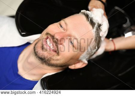 Hairdresser Washing Head Of A Young Man In Sink