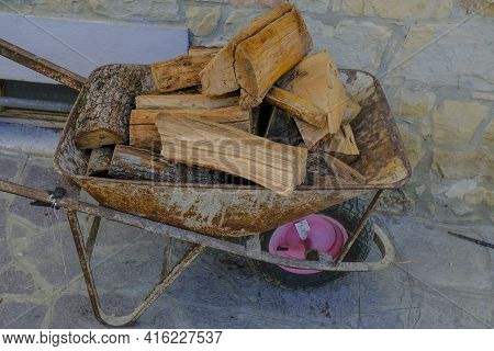 Firewood In The Metallic Barrow Close-up On The Backyard. Wood Chopping Process. Countryside Life. L