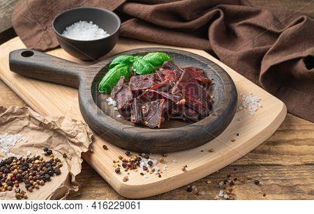 Slices Of Beef Jerky, Pepper, Salt, And Fresh Basil On A Beige Chopping Board. Jerky Meat In A Woode