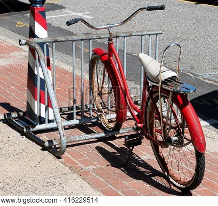 An Old Vintage Red Bicycle With A White Banana Seat Parked In A Bike Rack On The Sidewalk.