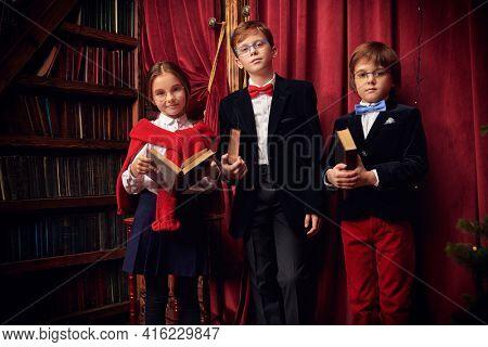 Group of modern children in elegant classic school uniform posing in a luxurious vintage library interior. Kid's school fashion.Elite training for children.