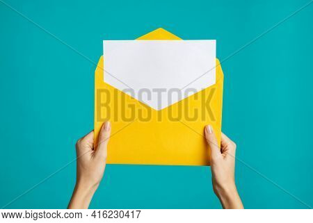 Women hand holding yellow envelope and card. Woman hands holding empty white card and open yellow envelope letter on blue background. Close up of girl showing empty letter ready for your text.