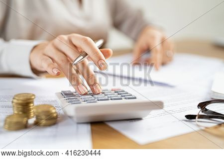Woman using a calculator doing a balance of monthly expenses. Close up of businesswoman working with financial data and using calculator with coins on desk. Calculating home finances and taxes.