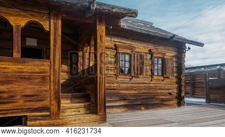 The Old One-storey House Is Built Of Wooden Planks And Logs. There Are Shutters On The Windows. Not