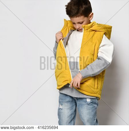 Teenage Guy In A Yellow Vest, Sleeveless Down Jacket With A Zipper And Jeans. He Felt Hot And Decide