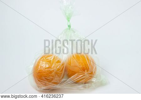 Oranges In A Plastic Bag On A White Background. Oranges On A Light Background. Buying Oranges