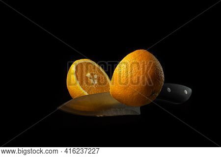 A Knife Cuts An Orange In The Air On A Dark Background. Orange Cut In Half On A Black Background. Cr