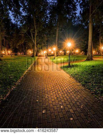 A Night Park Lit By Lanterns With A Stone Pavement, Trees, Fallen Leaves And Benches In Early Autumn