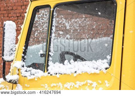 Bright Yellow Truck Cab In Bad Weather. The Glass Of The Truck Cab Is Covered With Snow.