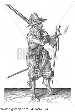 A Soldier, to the Right , who places a musket with his right hand on his left shoulder, pointing the barrel diagonally upwards. In his left hand a burning wick and a furket, vintage engraving.