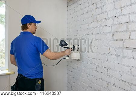 Man Painting Old Brick Wall In White Color With Paint Sprayer