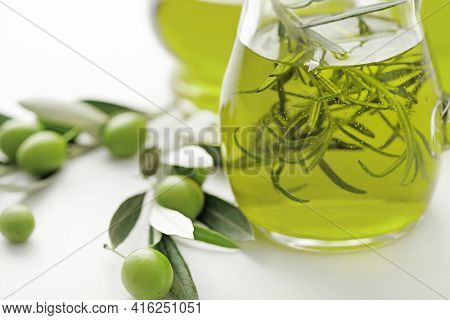 bottle of olive oil and green olives on white background
