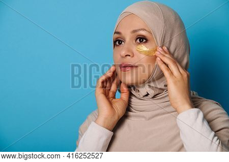 Closeup Portrait Of A Muslim Woman In Hijab Using Hydrogel Eye Patches, On Blue Background With Copy
