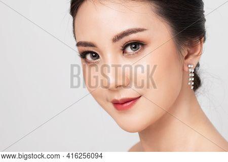Beautiful Makeup Asian Woman. Closeup Face Perfect Skin Of Asian Girl In Studio White Background. Be