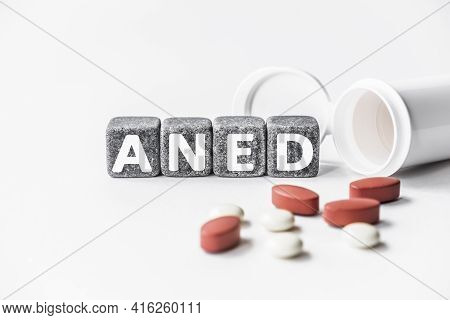 Word Aned Is Made Of Stone Cubes On A White Background With Pills. Medical Concept Of Treatment, Pre