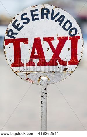 Urban Rusty Metal Sign In Colonia Del Sacramento Saying Taxi Parking Only With Blurred Background, U