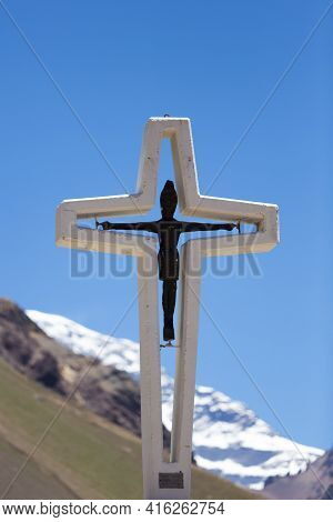Religious Cross With The Peak Of The Aconcagua Mountain With Clear Blue Sky, Argentina.