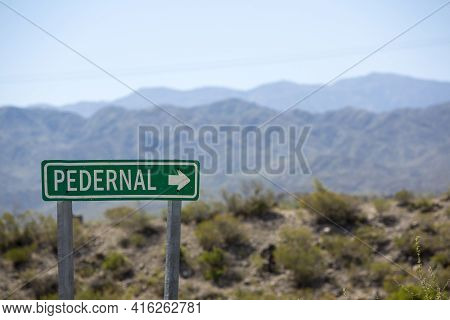 Wooden Sign Post Showing The Direction To Pedernal With The Dry And Arid Mountains In The Background