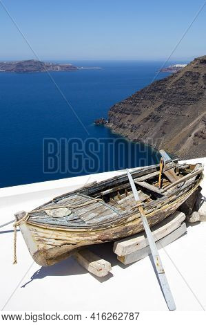 Santorini, Greece, July 24: Old Wooden Fisher Boat Standing On The Roof With View Of The Beautiful A