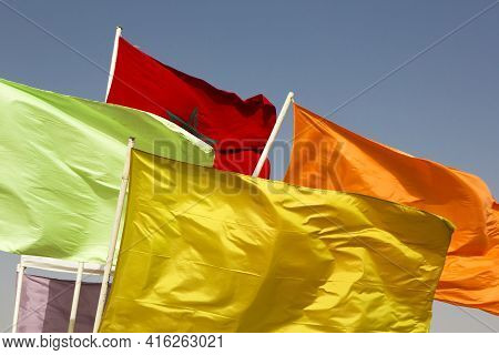 Various Colored Flags And The Flag Of Morocco Waving Against Blue Sky