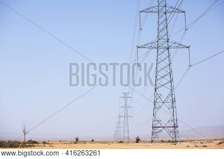 Electrical Towers Across A Desert Background And Blue Sky Near Tata, In The Hottest Region Of Morocc