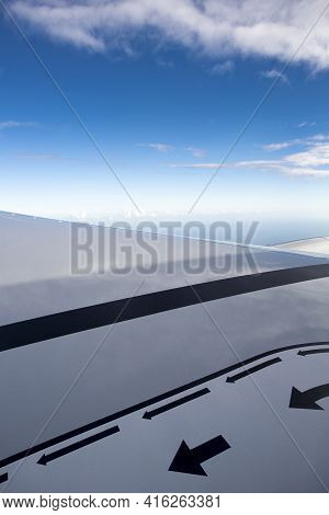 View Of Jet Plane Wing With Crystal Blue Sky In The Background And Safety And Security Markers Like
