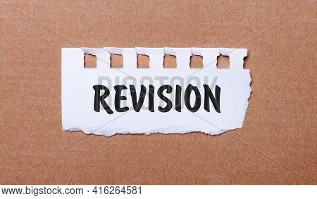 On A Brown Background, White Paper With The Inscription Revision