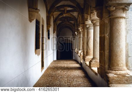 Passagge Through An Antique Medieval Cloister With White Wall And Stone Columns, Leading To A Distan
