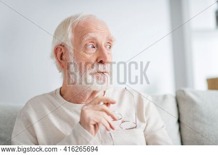 Photo Of Aged Man Pensioner Sit Sofa House Indoors Serious Think Minded Dream Dreamy Look Empty Spac
