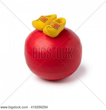 Whole Dutch red Edam cheese with a pair of souvenir wooden shoes on top isolated at white background