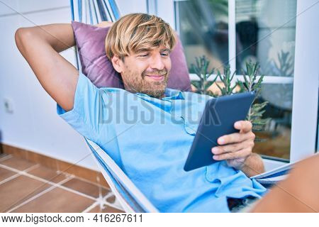 Middle age handsome man at the terrace of his house relaxing lying on a hammock with touchpad device