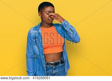 Young african american woman wearing casual clothes smelling something stinky and disgusting, intolerable smell, holding breath with fingers on nose. bad smell